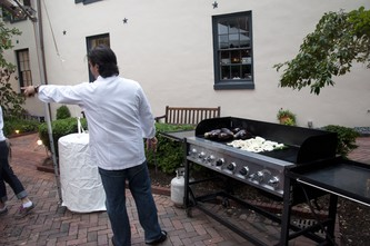 Chef Albisu loads the grill with Eggplant, Onions and Zucchini while directing his team.